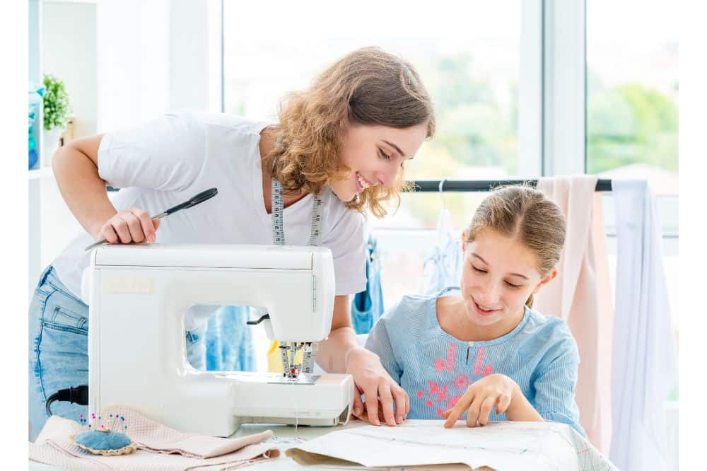 mother teaching her daughter how to use sewing machine